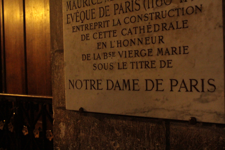 A plaque inside Notre Dame cathedral at night