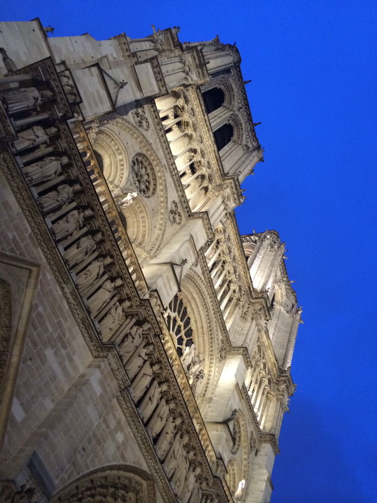 Looking up at a lit Notre Dame at night - front view