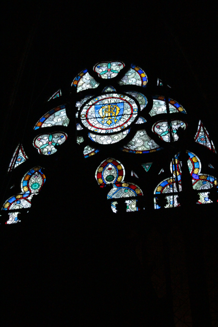 Stain glass window in the shadows in Notre Dame