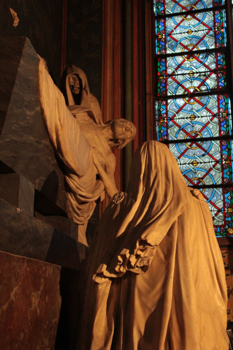 Statues inside Notre Dame with stain glass window