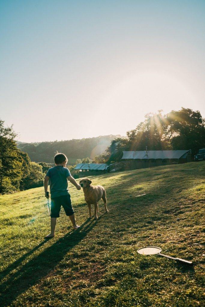 Exe Valley Glamping, Devon, boy and dog playing