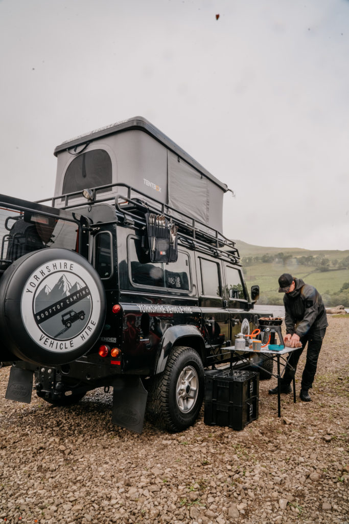 cooking outside land rover defender with roofbunk tent wild camping in Yorkshire