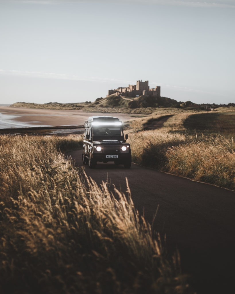landrover with rooftent driving bamburgh beach