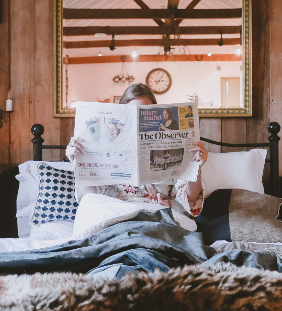 reading papers in bed at the Outbuildings self-catering studios in Dorset
