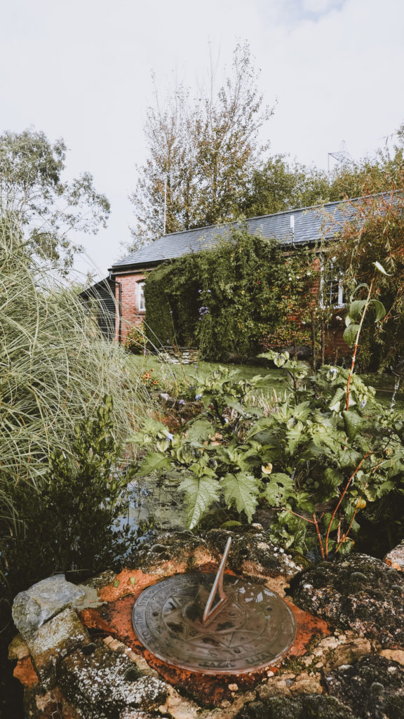 The Sty exterior and garden at the Outbuildings self-catering studios in Dorset